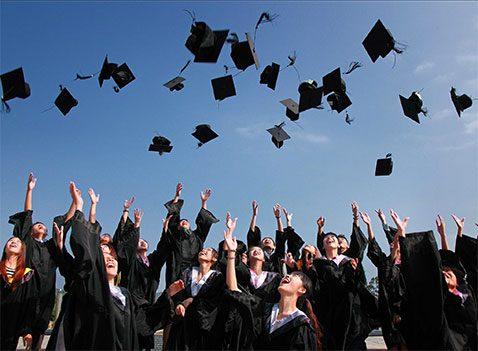 Graduates toss caps in the air